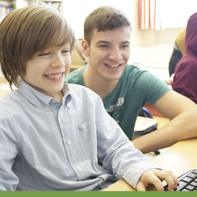 Two boys smiling while looking at a computer