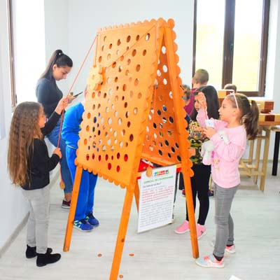 Girls move flower around easel with strings