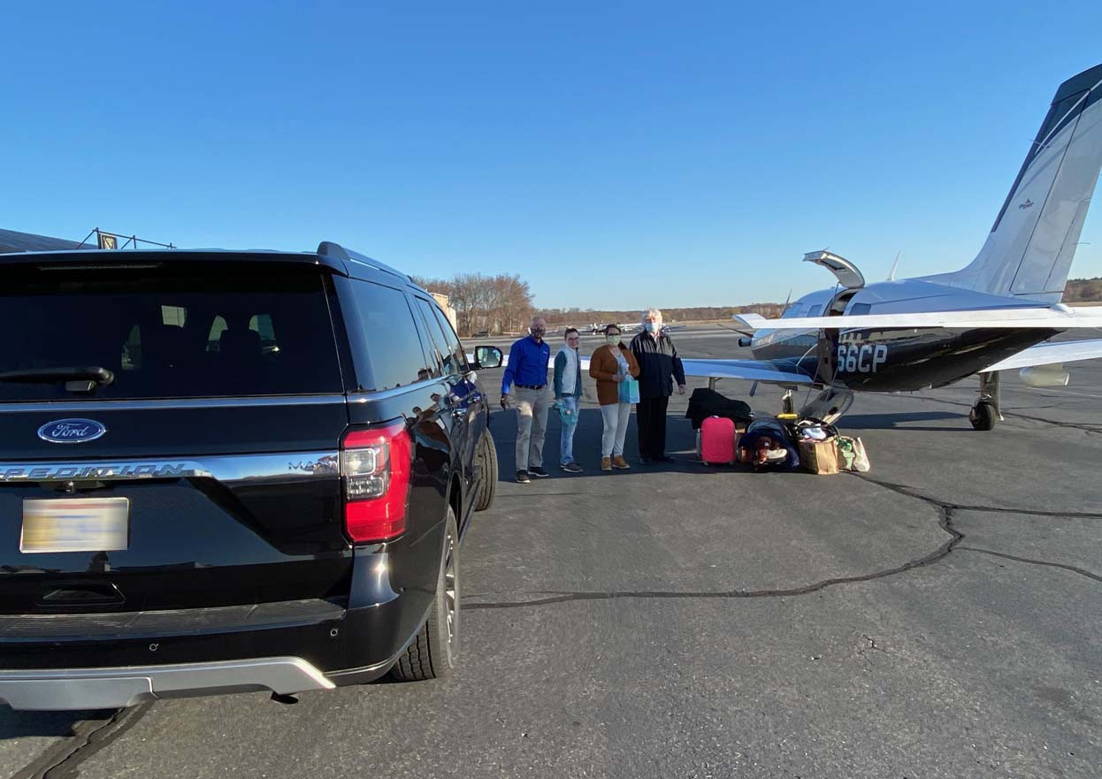 Four people and baggage on airport tarmac flanked by Ford vehicle and plane