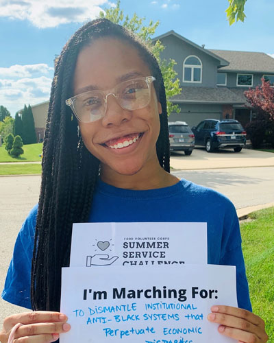 Black female wearing long braids wearing glasses and holding two sheets of paper horizontally with I'm Marching For: TO DISMANTLE INSTITUTIONAL ANTI_BLACK SYSTEMS that Perpetuate ECONOMIC [disparities #March4HOPE] atop FORD VOLUNTEER CORPS SUMMER SERVICE CHALLENGE