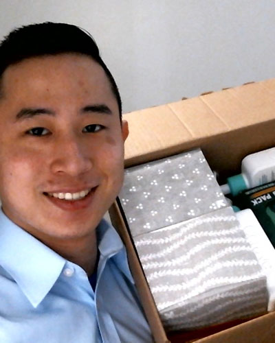 Head shot of Asian, male Abraham Huang wearing a blue dress shirt and holding a box of paper products and sanitation liquid in container with pump