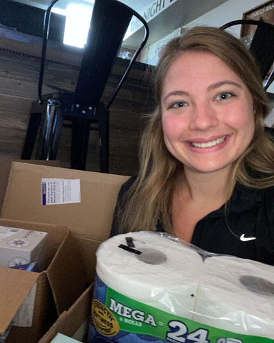 Head shot of light-skinned female with long light brown curly hair holding six roll package of toilet paper next to cardboard box of facial tissue boxes