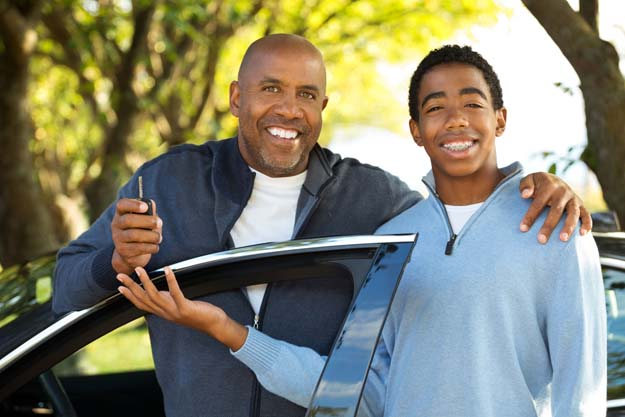 Father with car keys and son with outstretched hand near car door