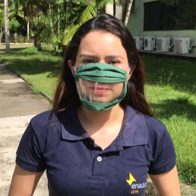 Female wearing mask with clear portion at mouth, wearing Enactus shirt.