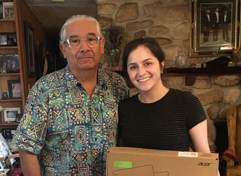 Older, thinning white-haired male in print shirt to right of young female in black T-shirt and jeans. She holds laptop box.They stand in a living room.