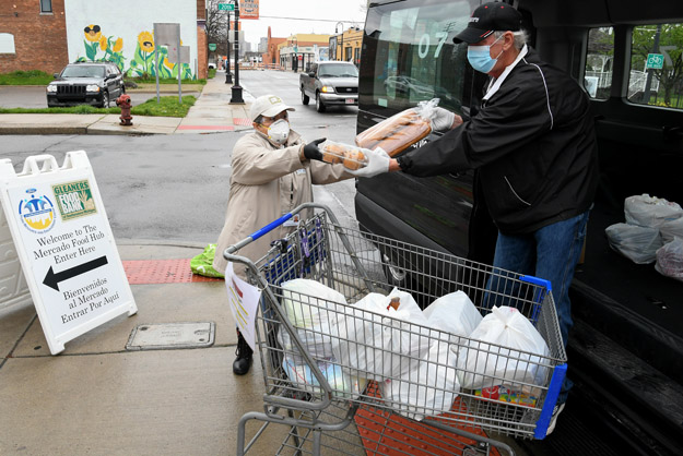 White-haired masked, gloved male hands packaged muffins and bread loves to masked and gloved female with grocery cart outside Southwest Detroit Ford Resource and Engagement Center.