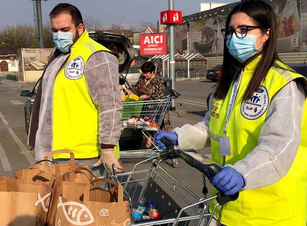 Male and female volunteers wearing light blue face masks and yellow FREC logo vests while pushing grocery cart with bags in parking lot