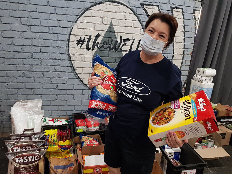 Holding family-size Kellogg All-Bran, value pack dry pasta masked female in Ford Choose Life T-shirt surrounded by canned, boxed food, paper goods