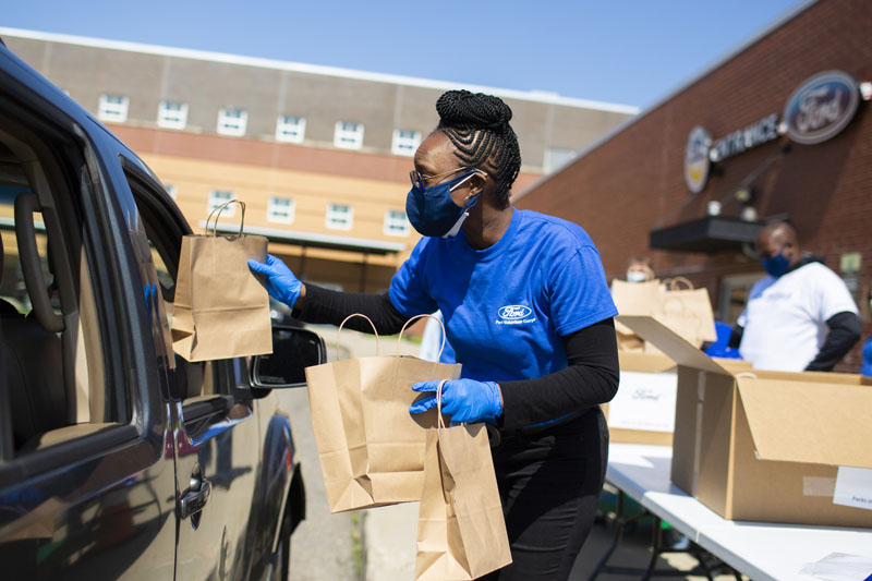 Masked, gloved African American female wearing blue Ford Community Corps T-shirt holding small brown paper bags extends one into vehicle outside Ford Resource and Engagement Center with additional volunteers and large boxes in background