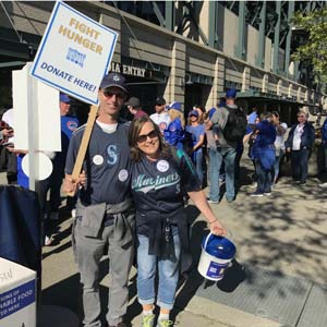 Male and female collecting peanut butter outside Seattle Mariners game