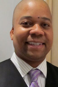 Bald, black male wearing white button-down dress shirt with dark pinstripes two-toned purple striped tie and black smock