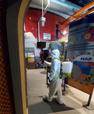 Individual wearing head-to-toe protective white suit with gloves and booties and backpack, holding a spray nozzle while walking through the museum.
