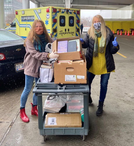 Two white females wearing face masks and latex gloves flank cart filled with books