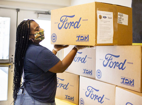 Masked and gloved African American female placing a large cardboard box,with blue script Ford printed on the side, atop five other boxes
