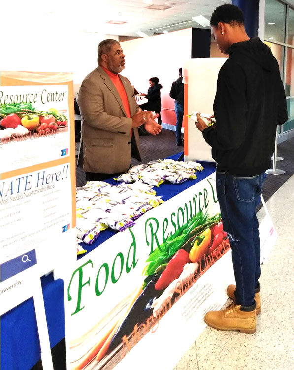 Collegiate age, male, African American student talking with older male at Food Resource Center display in Morgan State University