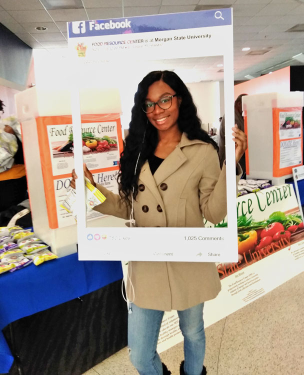 Collegiate age, female, African American student holding facebook frame displaying FOOD RESOURCE CENTER is at Morgan State University while standing in front of FRC display.