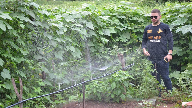 Male standing in a green garden with and irrigation sprinkler running